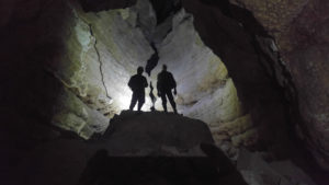 Two men in a dark cave passage