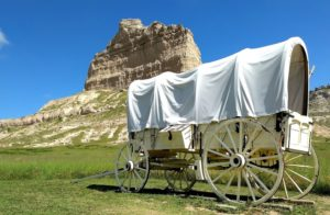 Towering bluff feature with a wagon cart in front of it