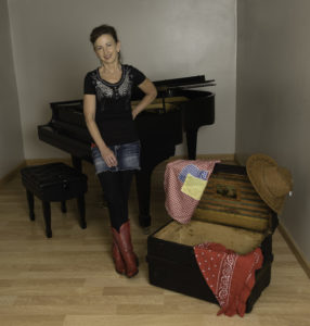 Photo of a woman standing next to a piano with red cowboy boots